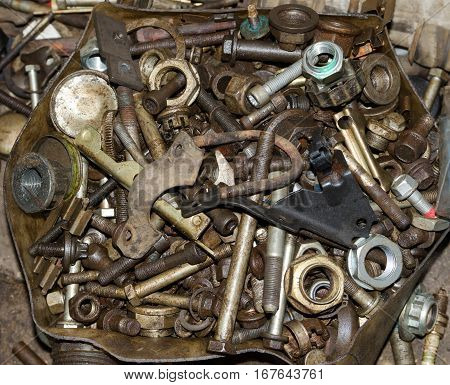 Old rusty worn out metal details bolts nuts bearings chain lie in a heap.