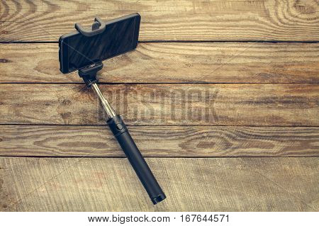 Mobile phone on selfie stick on old wooden background. Toned image.