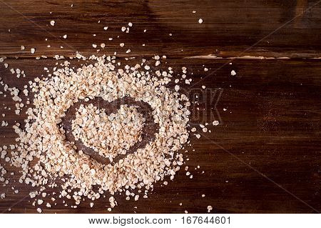 On vintage boards sprinkled on oatmeal on which is painted a heart in honor of Valentine's day.