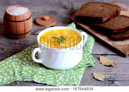 Light chicken rice soup in bowl, textile napkin, bay leaves, rye bread slices on wooden table. Soup cooked with chicken, white rice and vegetables. Homemade lunch or dinner. Closeup