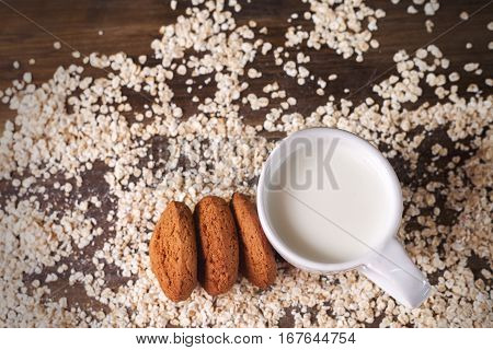 Oatmeal cookies on a background of oats next to a glass of milk on vintage board.