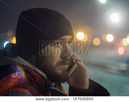 Man talking by smartphone at night bokeh light in background. Concept of night shift.