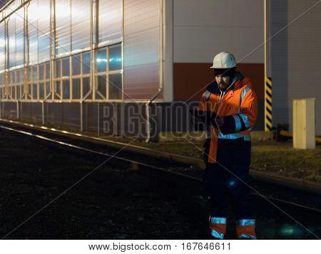 Young engineer working during hignt shift otdoors in helmet.