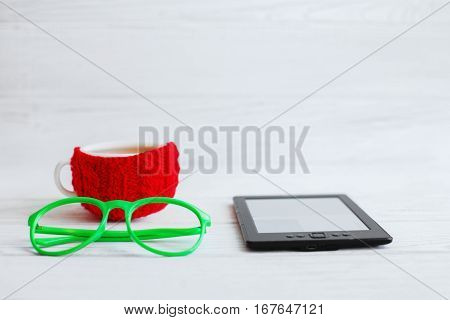 E-book glasses and a red cup of tea on a white background. The concept of modern technology and reading.