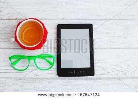 E-book glasses and a cup of tea on a white background. Top view. The concept of modern technology and reading.