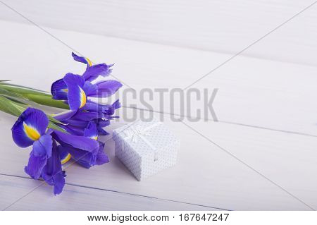 Bouquet Of Irises With Gift Box On White Wooden Background