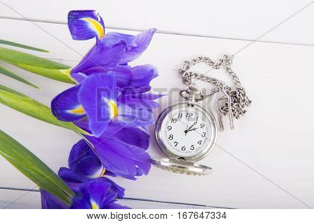 Bouquet Of Irises With Alarm Clock On White Wooden Background