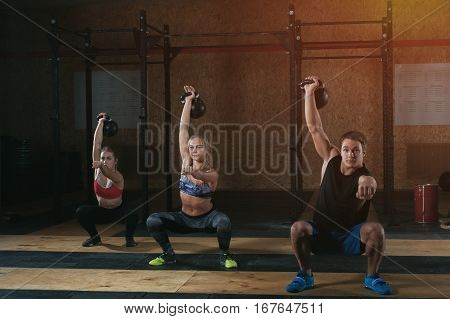 Three muscular adults doing squats with kettle bells over the head in gym. Weightlifting, power lifting workout. Sports, fitness concept.