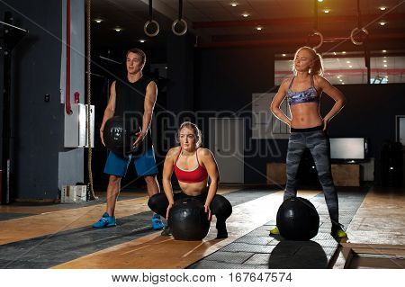 Group of muscular caucasian adults exercising with heavy balls in gym. Weightlifting training. Fitness, sports concept.