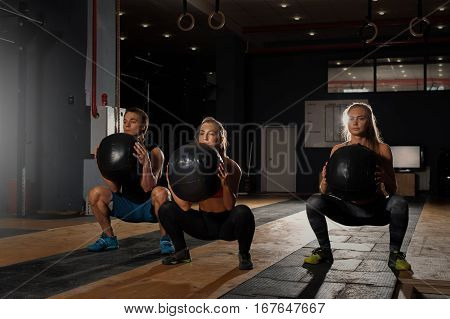 Group of sporty caucasian adults exercising in gym. Athletes doing squats with weights. Fitness, sports concept.