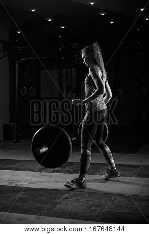 Strong sporty girl throw down barbell after exercise. Female athlete exercising with weights. Fitness, sports concept.