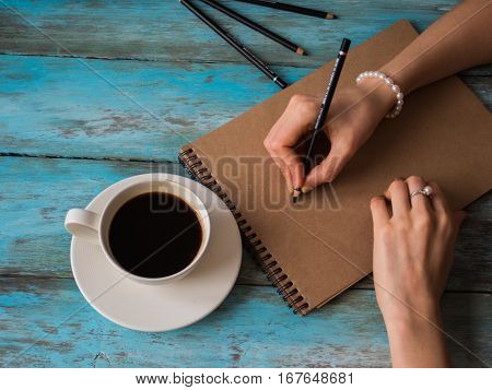 Writing woman at the cafe, cup of coffe and notepad