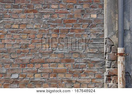 Damaged brick concrete wall and pipeline. Grunge background. Horizontal