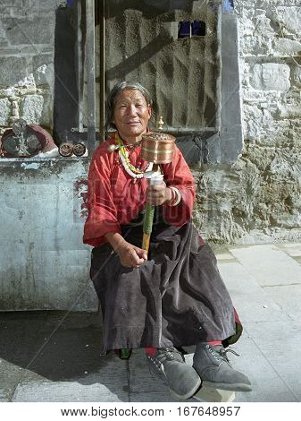 Lhasa, Tibet, China - September 2007: An elderly Tibetan pilgrim lady in big boots with prayer wheel on September 2007 in Lhasa, Tibet, China.