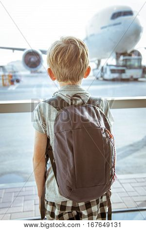 Young traveller looking at planes in the airport