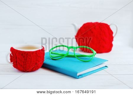 The book glasses a cup of tea and teapot on white wooden table. The concept of learning and work.