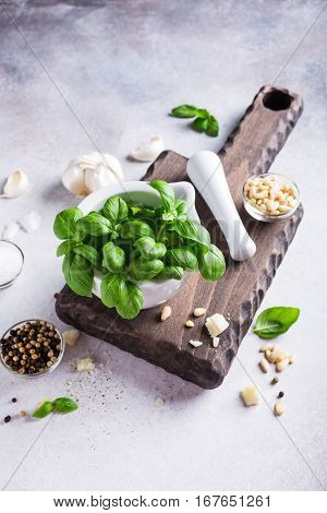 Ingredients for making green pesto sauce. Basil in white mortar on wooden cutting board. Healthy italian food. Copy space.