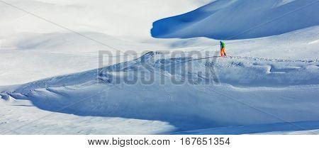 Freerider alpine skier walking in fresh powder snow. Wide composition