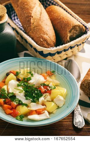Clear fish soup with vegetables on wooden background.
