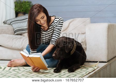 Sharing some ideas. Pleasant funny beautiful woman trying entertaining her Labrador while sitting with him on the floor during the weekend time