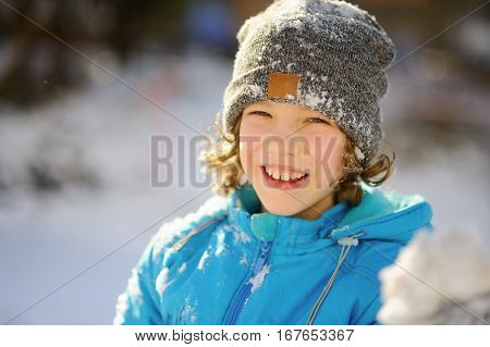 Winter portrait of the boy of younger school age. The nice fellow in a blue jacket and a gray knitted cap joyfully smiles. He rejoices to snow. Snow on clothes and the boy's hair in hand a snowball.