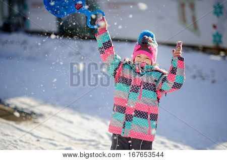 Girl of younger school age on walk in winter day. Child warmly is also brightly dressed. In hands at the girl the light-weight saucer sledge for driving from an ice slope.