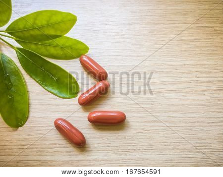 Brown vitamins on wooden background, Herbal capsules, vitamin supplemental, herbal tablets, herbal pills, vitamin pills on wood texture with soft morning light.