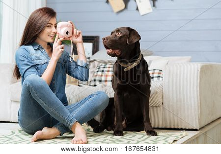 Like a professional. Elegant graceful pretty lady enjoying her hobby by making pictures of her beautiful Labrador while sitting near him on the floor
