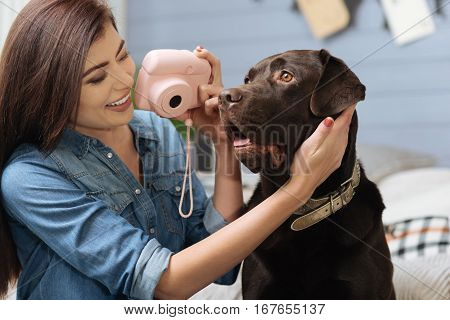 Be my model. Cute emotional smiling woman tilting her dogs head trying making a perfect photograph of him during her free time
