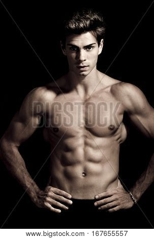 Italian model muscular man. Nude portrait. A young Italian boy shirtless posing on a grunge background. Muscular and athletic. Well-defined muscles.