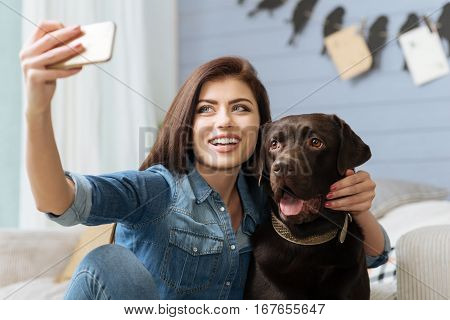 One more time. Emotional pretty smiling woman making a selfie of herself with a Labrador using her smartphone while staying home during weekend