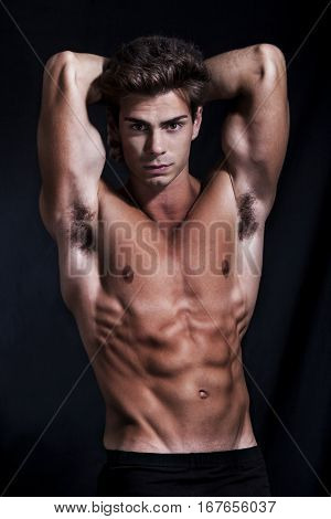 Sculptural man model perfect muscular body. A fascinating and sculptural male model is posing showing off her body. He has an athletic body and muscular. Perfect proportions with sculpted abs. He has his hands behind his head showing his biceps also.