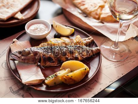 Grilled mackerel with vegetables, sauce and wine on a ceramic plate in a restaurant. Tasty healthy dish of fish. Useful vitamins nutrition.