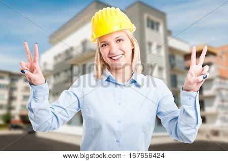 Blonde Lady Engineer Wearing Helmet Showing Peace