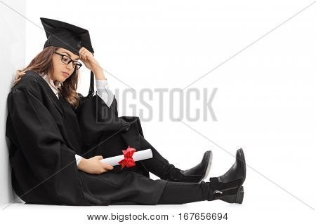 Depressed graduate student with a diploma sitting on the floor and leaning against a wall isolated on white background