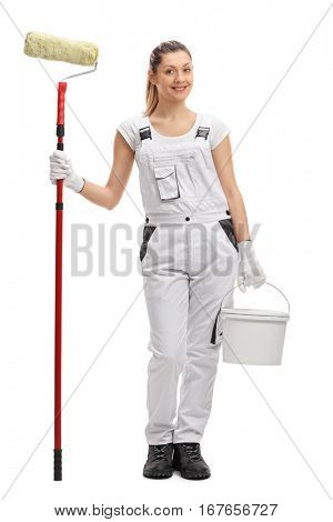 Full length portrait of a happy female decorator with a paint roller and a paint bucket isolated on white background