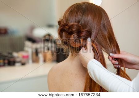 Beautiful red-haired girl with long hair hairdresser weaves a French braid in a beauty salon. Professional hair care and creating hairstyles.