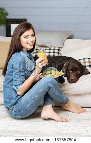 Tasty snacks. Stylish tender brunette girl eating a delicious midday meal while spending her time at home with her dog staying beside her at all times