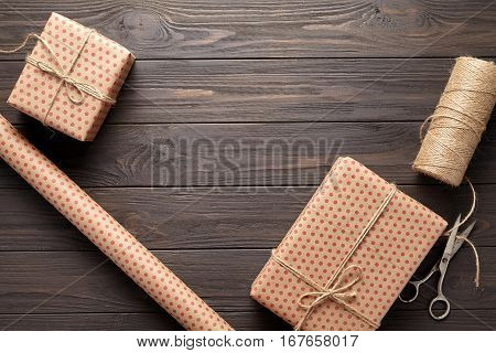 Box with a gift, wrapping paper, scissors, twine. table ideas for wrapping gifts for birthdays and holidays. Rustic style and dark wood background.
