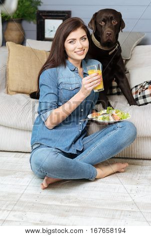 Tasty and good. Wonderful elegant pretty girl eating a nutritious lunch while spending her time in a living room and sitting on the floor beside her adorable pet