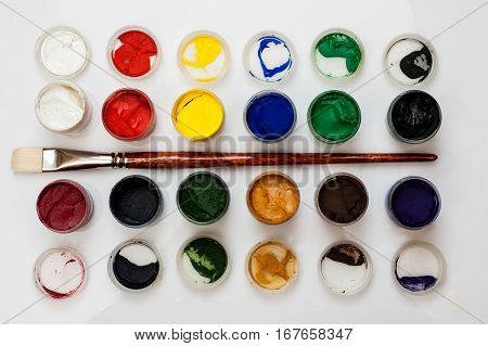 Many Open Jars With Paint And Brush Among Them On A White Background, Top View