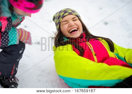 The charming young woman lies on snow. She is dressed in a bright jacket and a knitted cap. The woman rejoices to winter and snow. She cheerfully laughs. Someone was inclined over her.
