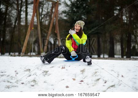 The young woman preparing to move out from the snow hill on a sled. The first snow has slightly covered the earth. The woman in a bright ski suit with pleasure spends the day off in the winter park.
