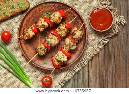 Traditional delicious turkey shish kebab skewer barbecue meat with tomatoes, pepper and sauce on ceramic dish. Served on wooden table background. Rustic style, natural light. Picnic bbq gourmet.