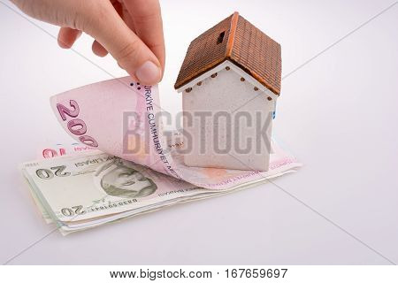 Hand Holding Turkish Lira Banknotes By The Side Of A Model House