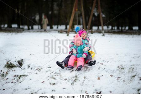 Two little girls together move down from a hill on the saucer sled. In the winter park it is snowing. Children are dressed in warm and bright ski suits. The earth is hardly covered with the first sno