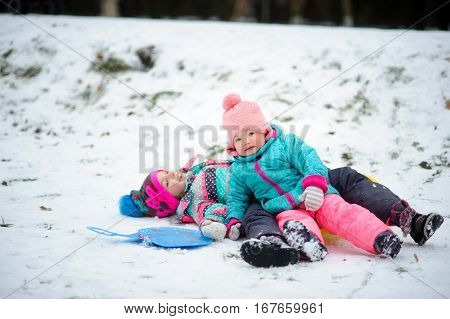 Two little girls in bright ski suits moved out with a snow slide. Children lie on snow and smile. They have rosy cheeks. Girls are glad to winter and snow.