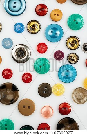Close-up Shot Of Many Different Buttons On A White Background, Flat Lay Pattern, Vertical.