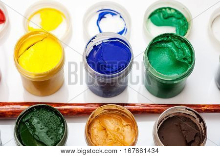 Many Open Jars With Paint And Brush Among Them On A White Background, Angle View