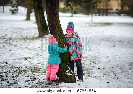 Two little girls stand near a big tree in winter park. It is snowing. Children are dressed in bright ski suits. Younger girl has embraced a tree trunk. Girl is more senior with love looks at baby.